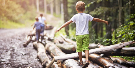 Children walking on fallen trees in the woods.