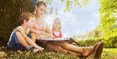 A woman reading to her children in an outdoor setting.